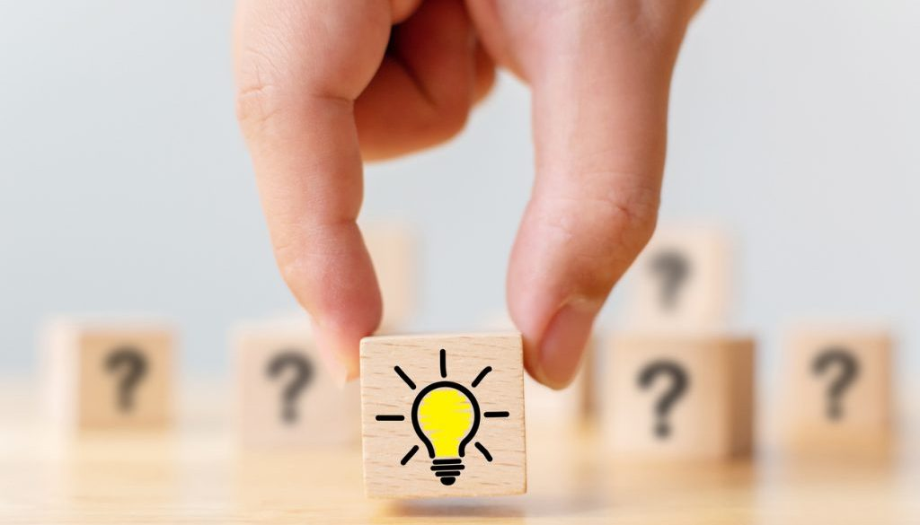 Concept creative idea and innovation. Hand picked wooden cube block with question mark symbol and light bulb icon